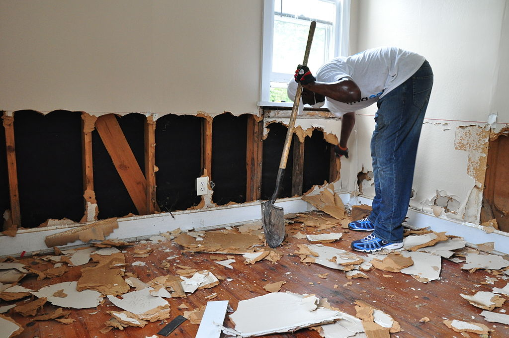 cutting drywall out for flood damage